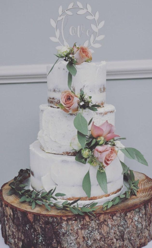 Modern floral buttercream cake with fresh flower cascade