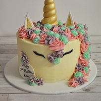 a buttercream unicorn cake with pink, turquoise and mauve icing
