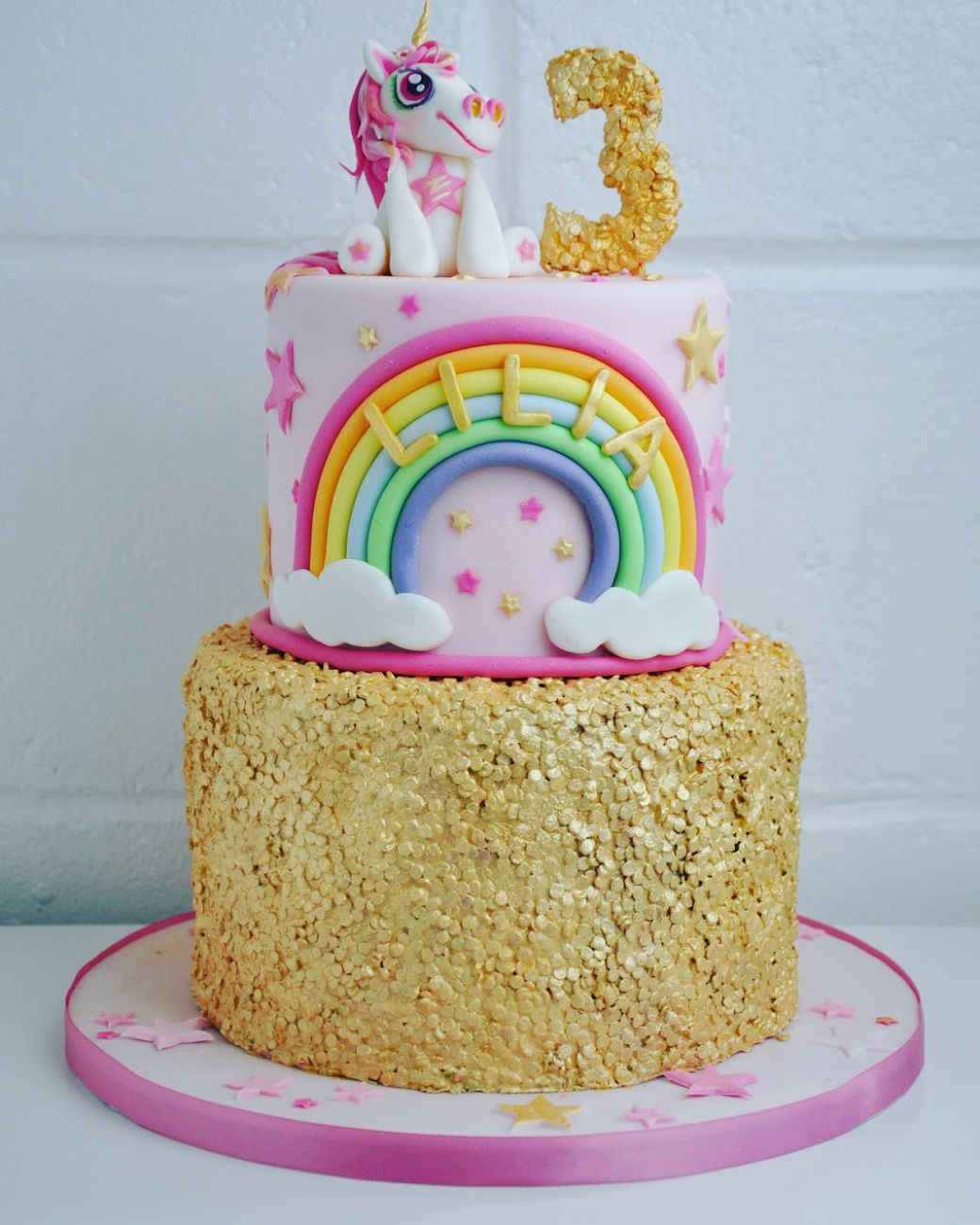 a two tiered gold, white and rainbow cake with a unicorn on top