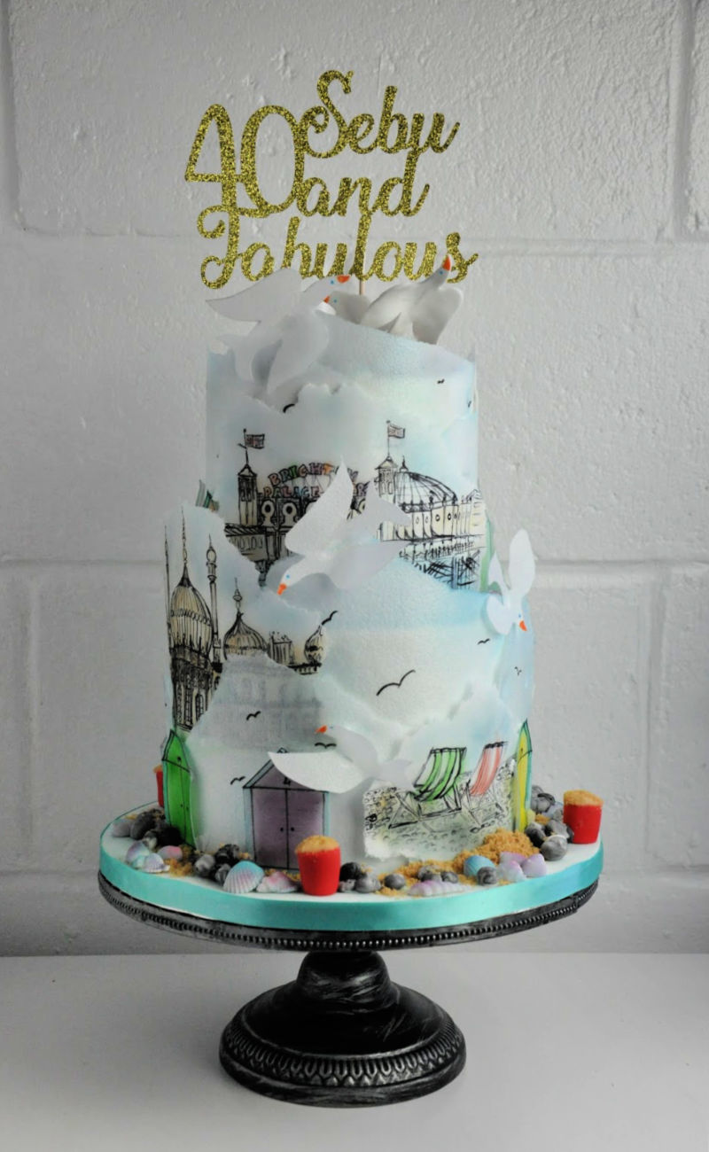 two tier brighton-themed cake with rice paper hand painted drawings on it
