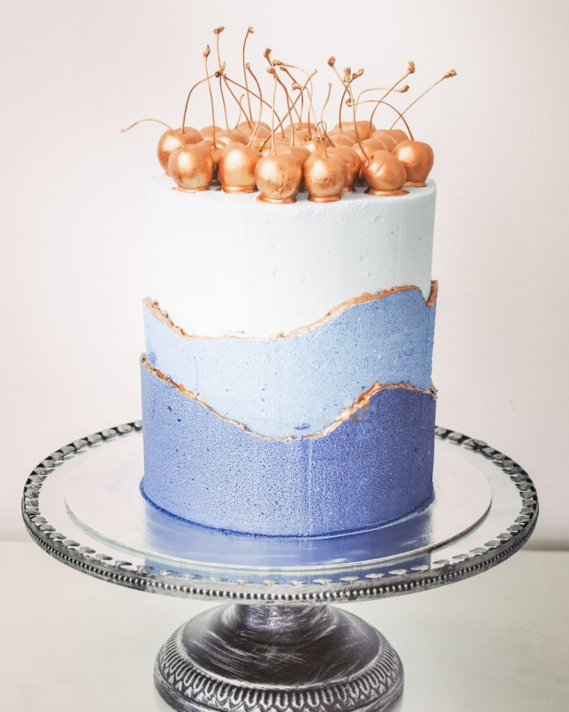 A blue ombre buttercream cake with gold cherries on the top of it