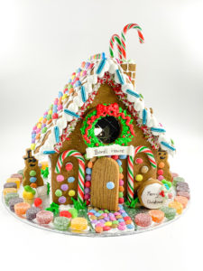 a very colourful gingebread house with candy canes on the front
