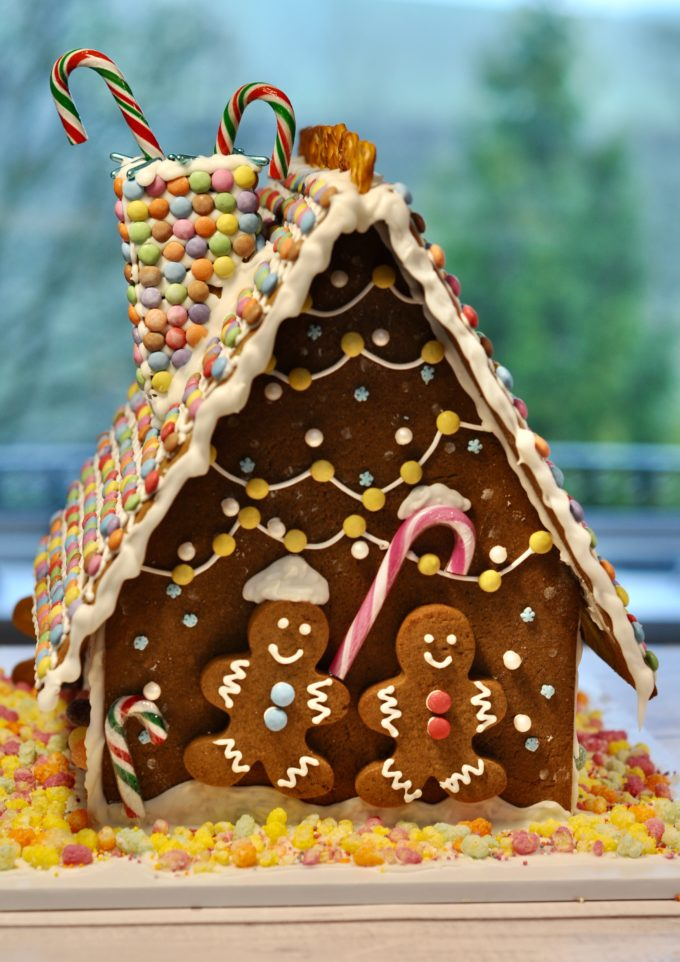 two gingerbread men holding hands on the back of a house