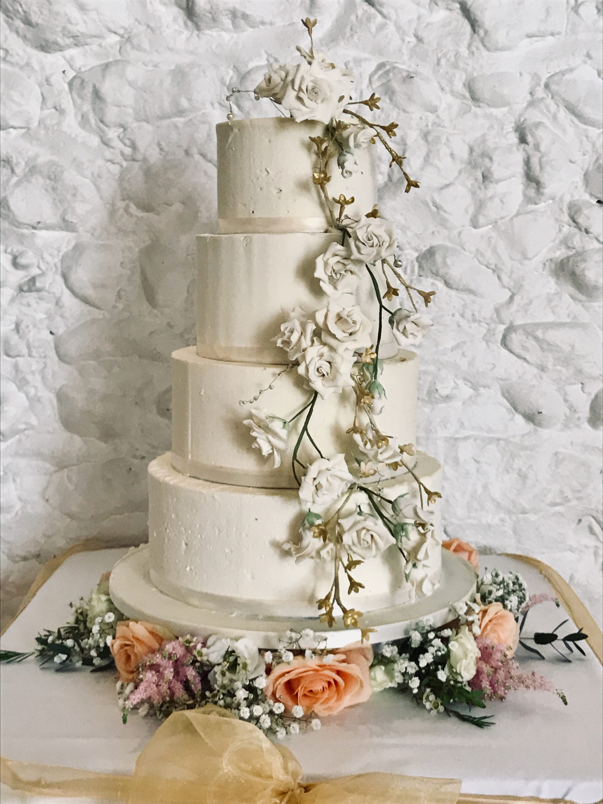 White buttercream wedding cake with sugar roses cascading down the front